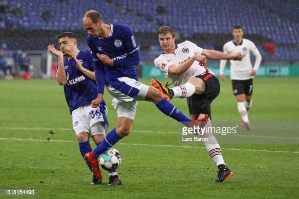 Martin Hinteregger of Eintracht Frankfurt takes a shot past Blendi Idrizi and Jonas Michelbrink of FC Schalke 04 during the Bundesliga match between...
