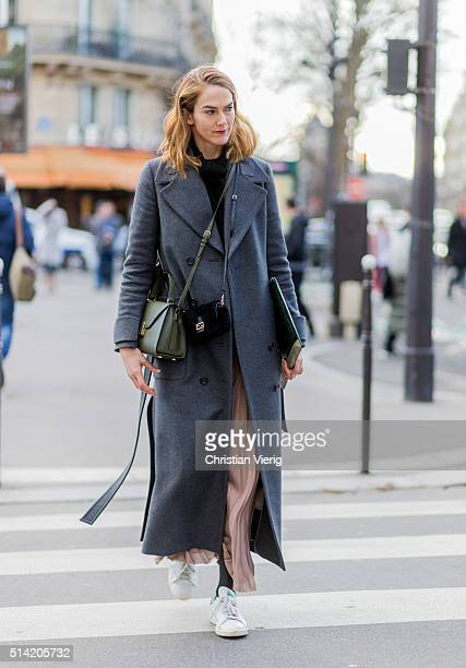 JJ Martin is wearing a grey wool coat and sneaker outside Hermes during the Paris Fashion Week Womenswear Fall/Winter 2016/2017 on March 7 2016 in...