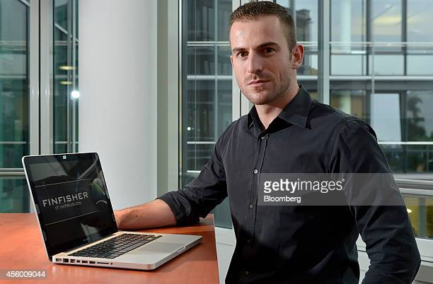 Martin J Muench managing director of Gamma International GmbH poses for a photograph beside an Apple Inc laptop displaying a Finfisher logo in Munich...
