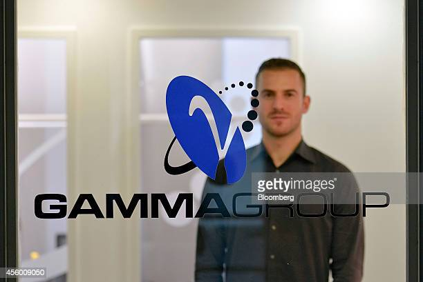 Martin J Muench managing director of Gamma International GmbH stands behind the Gamma Group logo as he poses for a photograph in Munich Germany on...