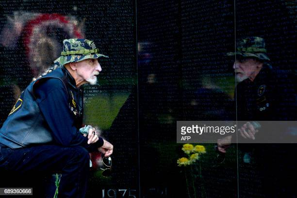 TOPSHOT Martin Jester of Florida pauses as he looks at the names on the wall of the Vietnam Veterans Memorial in Washington DC May 28 2017...