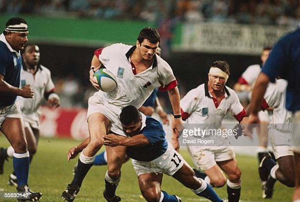 Martin Johnson of England is tackled by Fata Sini of Western Samoa during the Rugby World Cup 1995 Pool B match between England and Western Samoa...
