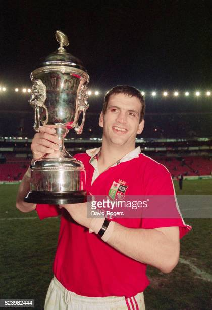 Martin Johnson, the British Lions captain, holds aloft the trophy after the third test match against South Africa at Ellis Park on July 5, 1997 in...