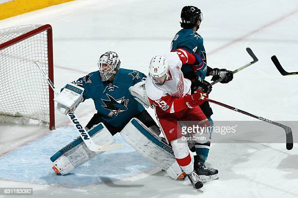 Martin Jones and Brenden Dillon of the San Jose Sharks defend against Riley Sheahan of the Detroit Red Wings during a NHL game at SAP Center at San...