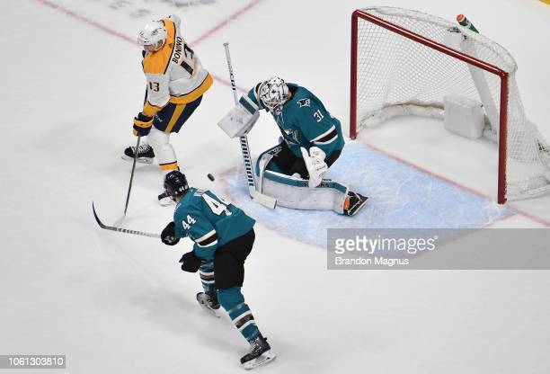 Martin Jones and MarcEdouard Vlasic attempt to stop the puck against Nick Bonino of the Nashville Predators at SAP Center on November 13 2018 in San...