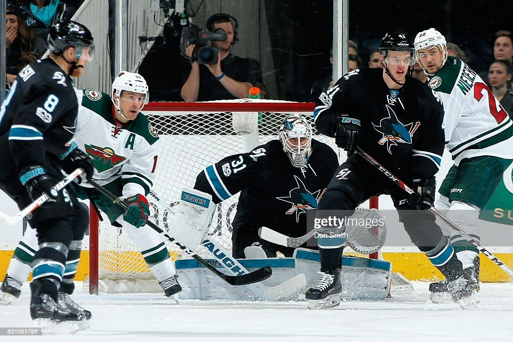 Martin Jones #31 and Mirco Mueller #41 of the San Jose Sharks along with Zach Parise #11 and Nino Niederreiter #22 of the Minnesota Wild watch the puck during a NHL game at SAP Center at San Jose on January 5, 2017 in San Jose, California.
