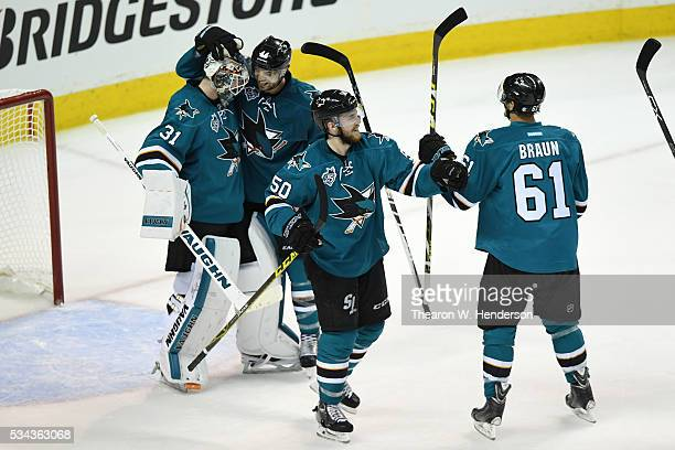 Martin Jones of the San Jose Sharks celebrates with Marc-Edouard Vlasic, Chris Tierney and Justin Braun after defeating the St. Louis Blues 5-2 in...