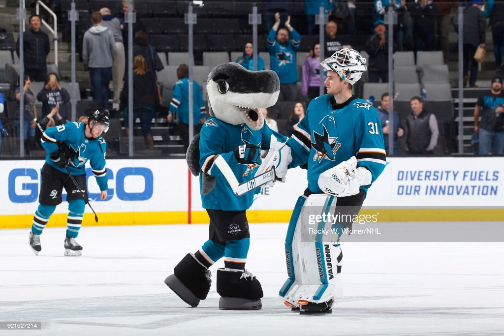 Martin Jones #31 of the San Jose Sharks celebrates with mascot S.J. Sharkie after defeating the Vancouver Canucks at SAP Center on February 15, 2018 in San Jose, California.