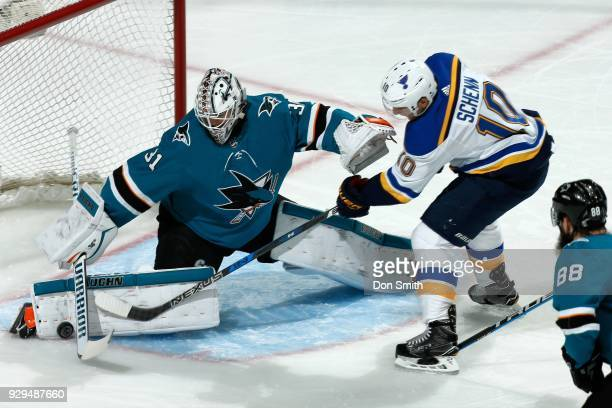 Martin Jones of the San Jose Sharks makes a pad save as Brayden Schenn of the St Louis Blues looks for the rebound at SAP Center on March 8 2018 in...