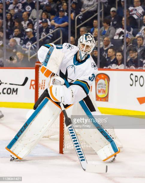 Martin Jones of the San Jose Sharks plays the puck to the side of the net during first period action against the Winnipeg Jets at the Bell MTS Place...