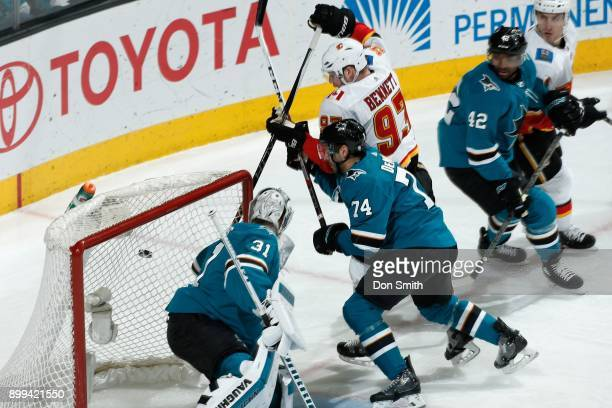 Martin Jones of the San Jose Sharks protects the net as Dylan DeMelo of the San Jose Sharks and Sam Bennett of the Calgary Flames scramble for the...