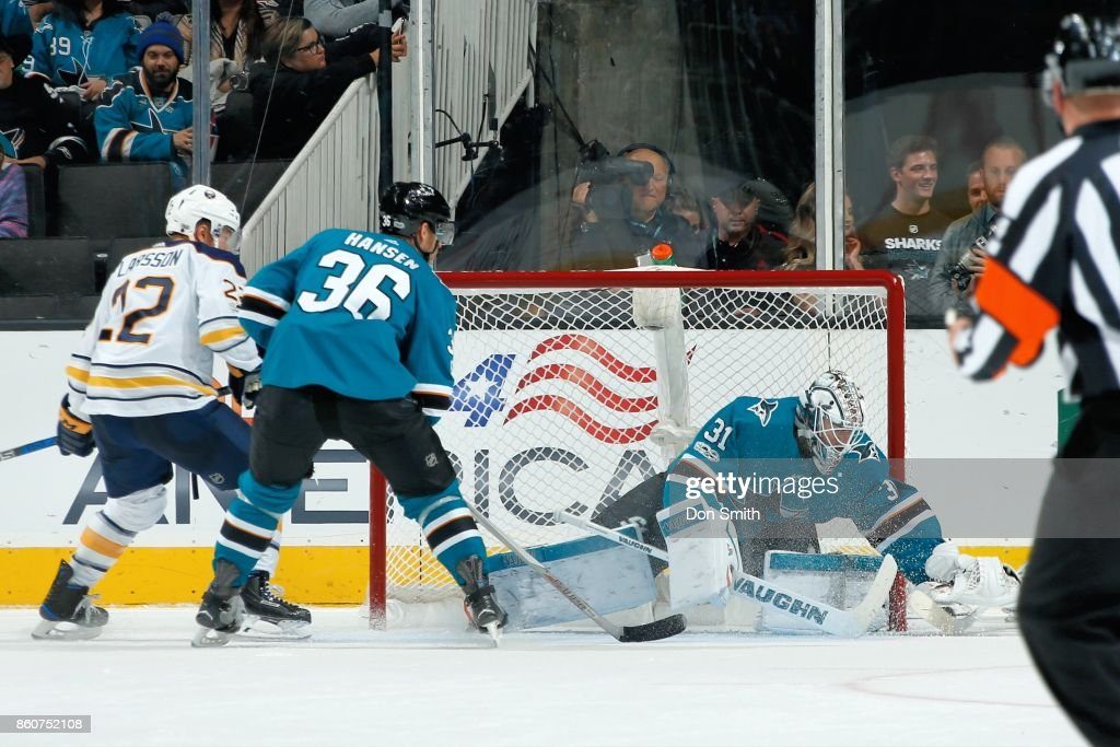 Martin Jones #31of the San Jose Sharks makes a save while Johan Larsson #22 of the Buffalo Sabres and Jannik Hansen #36 of the San Jose Sharks look at SAP Center at San Jose on October 12, 2017 in San Jose, California.