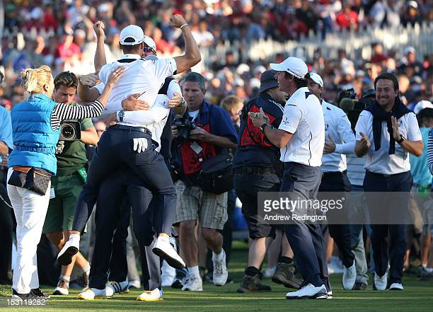 Martin Kaymer is mobbed by the European team after he holed the decisive putt on the 18th green during the Singles Matches for The 39th Ryder Cup at...