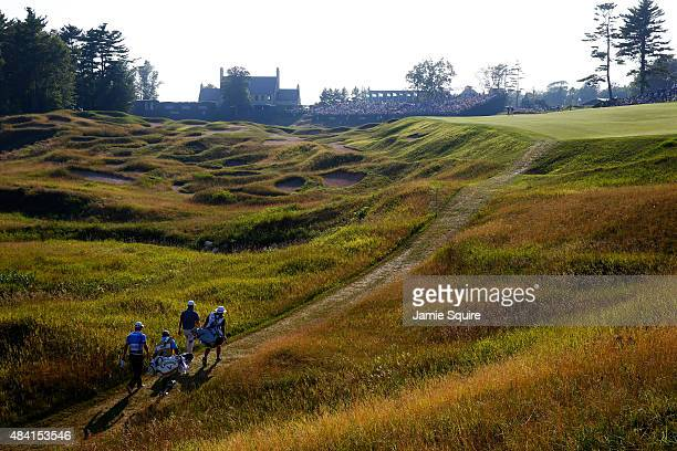 Martin Kaymer of Germany and Branden Grace of South Africa walk with their caddies up the 18th hole during the third round of the 2015 PGA...