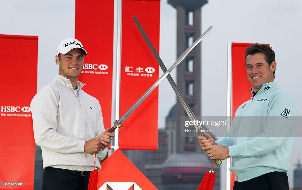 Martin Kaymer of Germany (L) and Lee Westwood of England cross swords during the 2010 WGC-HSBC Champions Photocall at The Peninsula hotel on The Bund, Shanghai on November 2, 2010 in Shanghai, China.