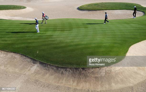 Martin Kaymer of Germany Dustin Johnson of the United States and Fabrizio Zanotti of Paraguay walk on the 18th hole during round three of the Abu...
