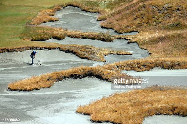 Martin Kaymer of Germany hits a shot from a bunker during a practice round prior to the start of the 115th US Open Championship at Chambers Bay on...