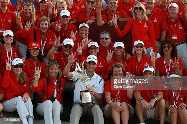 Martin Kaymer of Germany holds the trophy in amongst a group of tournament marshalls after winning the 2011 Abu Dhabi HSBC Golf Championship held at...
