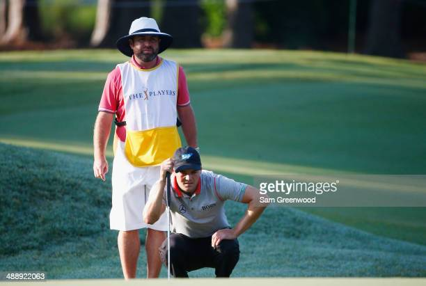 Martin Kaymer of Germany lines up a putt with his caddie Craig Connelly during the second round of THE PLAYERS Championship on The Stadium Course at...
