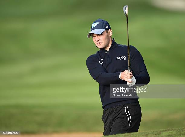 Martin Kaymer of Germany looks on after playing a bunker shot during the continuation of the weather delayed first round of the Porsche European Open...