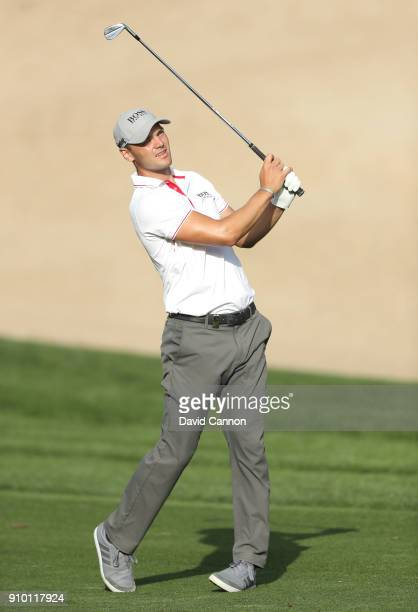 Martin Kaymer of Germany plays his second shot on the par 414th hole during the first round of the Omega Dubai Desert Classic on the Majlis Course at...
