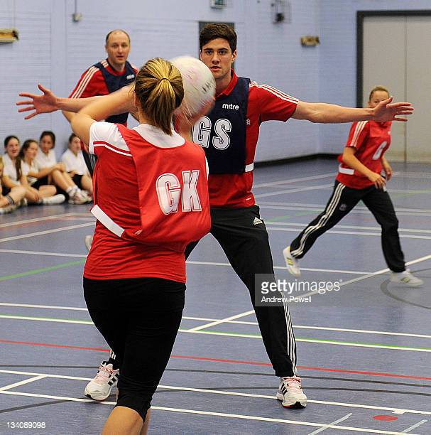 Martin Kelly of Liverpool FC attempts to block a pass from Jordyn Layfield during an exhibition netball game with women from the LFC Foundation...