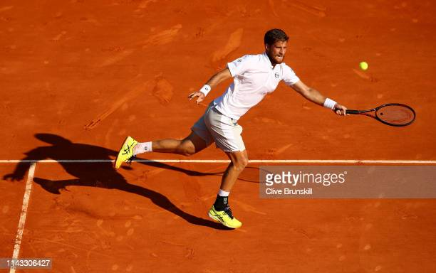 Martin Klizan of Slovakia plays a forehand volley against Dominic Thiem of Austria in their second round match during day four of the Rolex...