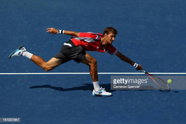 Martin Klizan of Slovakia returns a shot against Jo-Wilfried Tsonga of France during their men's singles second round match on Day Four of the 2012...