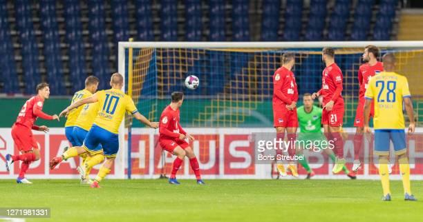 Martin Kobylanski of Eintracht Braunschweig scores his team's first goal past goalkeeper Alexander Schwolow of Hertha BSC during the DFB Cup first...