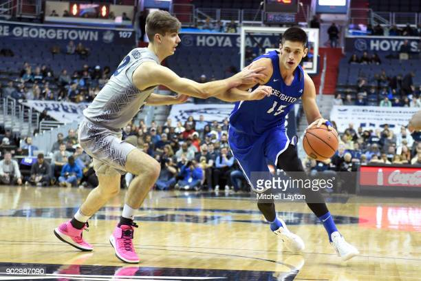 Martin Krampelj of the Creighton Bluejays dribbles around George Muresan of the Georgetown Hoyas during a college basketball game at the Capitol One...