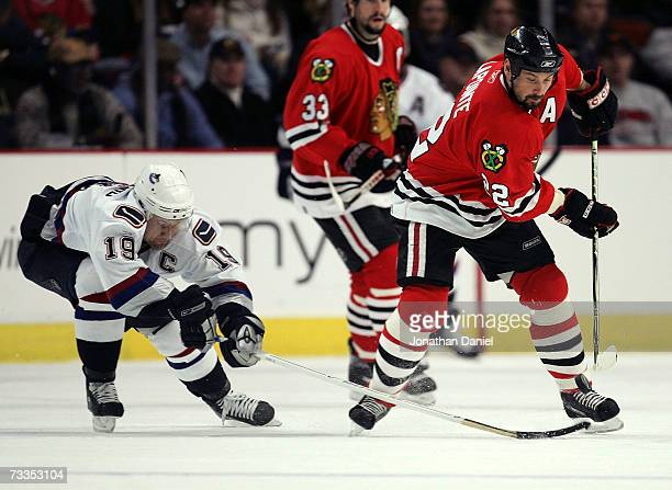 Martin Lapointe of the Chicago Blackhawks knocks the puck away from Markus Naslund of the Vancouver Canucks on February 16 2007 at the United Center...