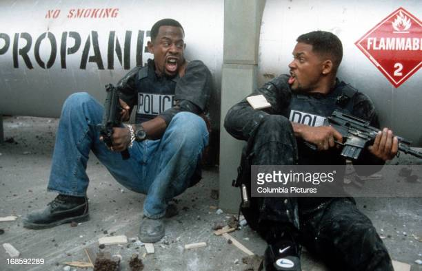 Martin Lawrence and Will Smith yelling at each other while holding machine guns to defend themselves in a scene from the film 'Bad Boys' 1995