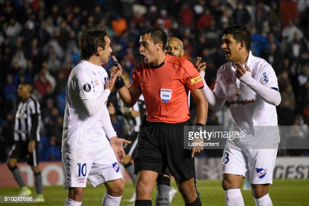 Martin Liguera and Diego Polenta argue with the referee Julio Bascuñán during a first leg match between Nacional and Botafogo as part of Copa...