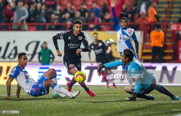 Martin Lucero of Tijuana kicks and scores the first goal of his team as Moisés Muñoz goalkeeper of Puebla attempts to cath the ball during the 4th...
