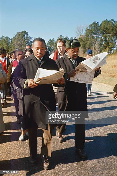 Martin Luther King and Ralph Abernathy reading newspapers during the march from Selma to Montgomery protesting the lack of voting rights for African...