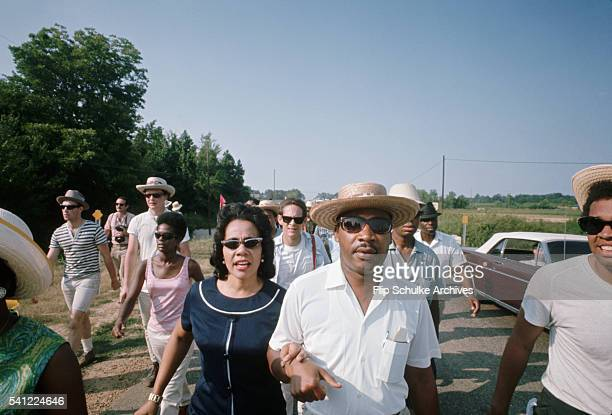 Martin Luther King Jr and his wife Coretta march together along a rural Mississippi road with the March Against Fear