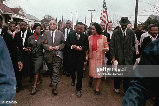 Martin Luther King Jr and his wife Coretta march with other civil rights activists through a neighborhood in Selma