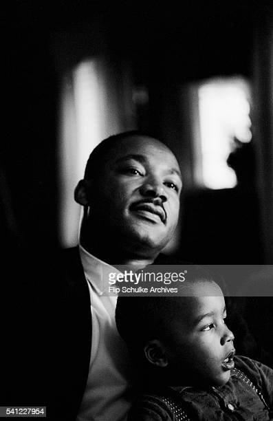 Martin Luther King Jr holds his son Dexter on his lap at home