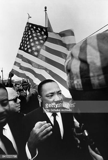Martin Luther King Jr in front of a waving American flag leads the final march from Selma to Montgomery