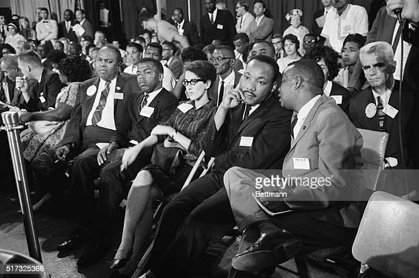 Martin Luther King Jr joins other leaders of civil rights movement as they listen to testimony before the credentials committee Shown are James...