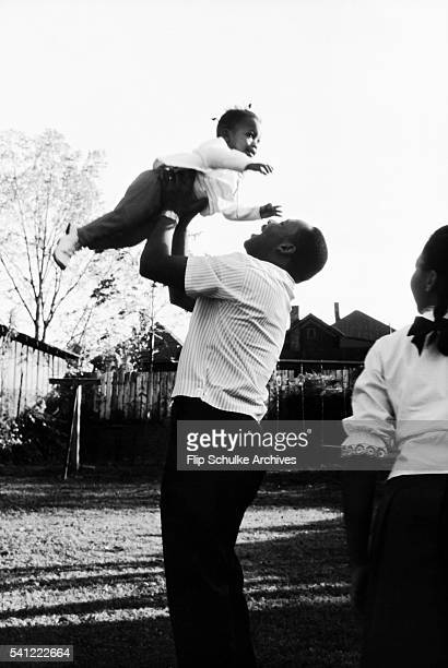 Martin Luther King Jr lifts his daughter Bernice as he plays with his children in the backyard of their Atlanta home
