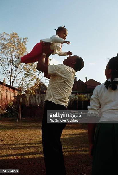 Martin Luther King Jr lifts his daughter Bernice as he plays with his daughters in their backyard