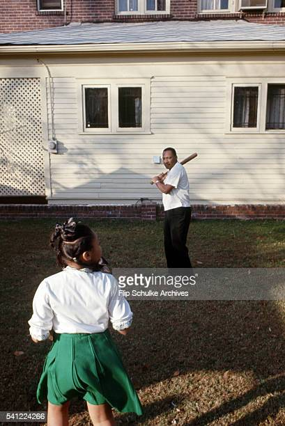 Martin Luther King Jr plays baseball with his daughter Yolanda in their backyard