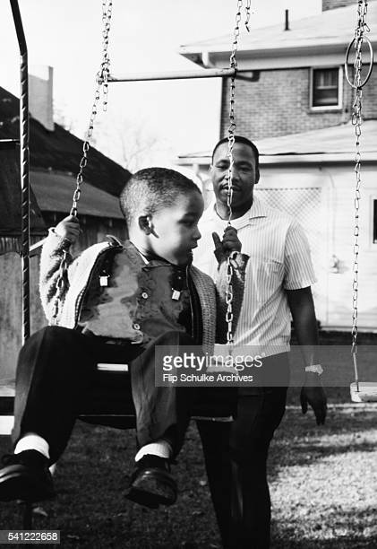 Martin Luther King Jr pushes his son Dexter on a swing in the backyard of their Atlanta home