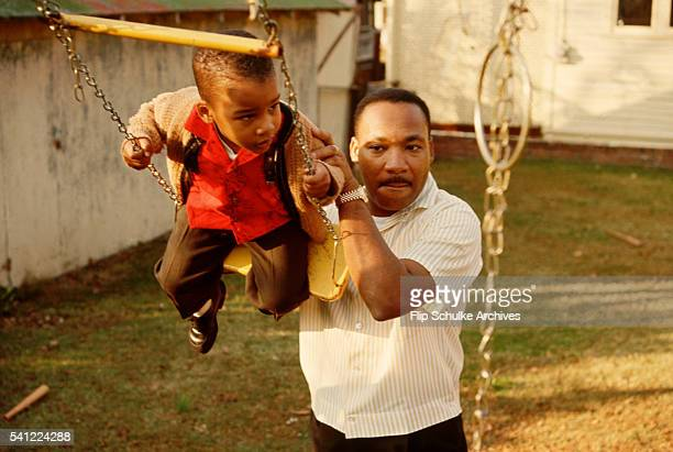 Martin Luther King Jr pushes his young son Dexter on a swing set in their backyard