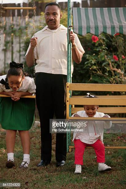 Martin Luther King Jr pushes his youngest daughter Bernice on a glider swing in their backyard