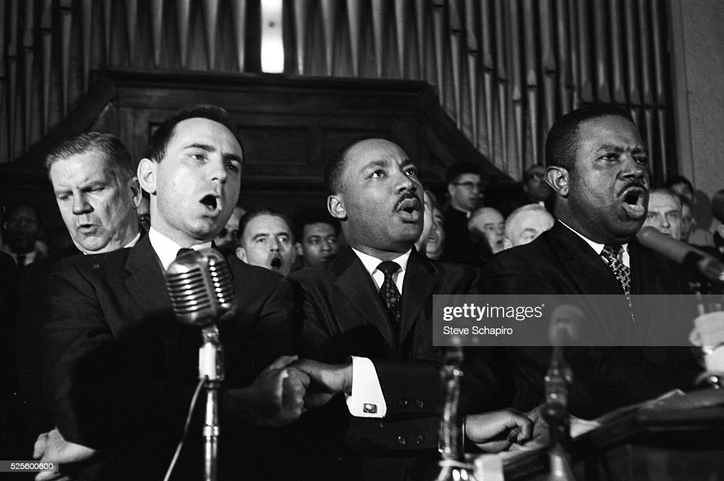 Martin Luther King Jr., Ralph abernathy and unidentified men sing in a Selma, Alabama church