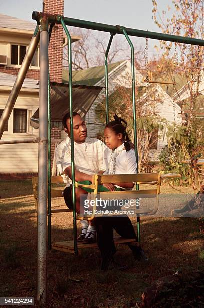 Martin Luther King Jr talks with his daughter Yolanda on a swing in their backyard