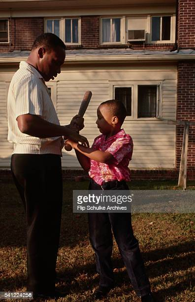 Martin Luther King Jr teaches his son Marty how to hold a baseball bat in their backyard