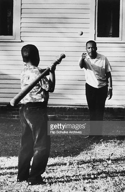 Martin Luther King Jr throws a baseball for his son to hit in the backyard of their Atlanta home
